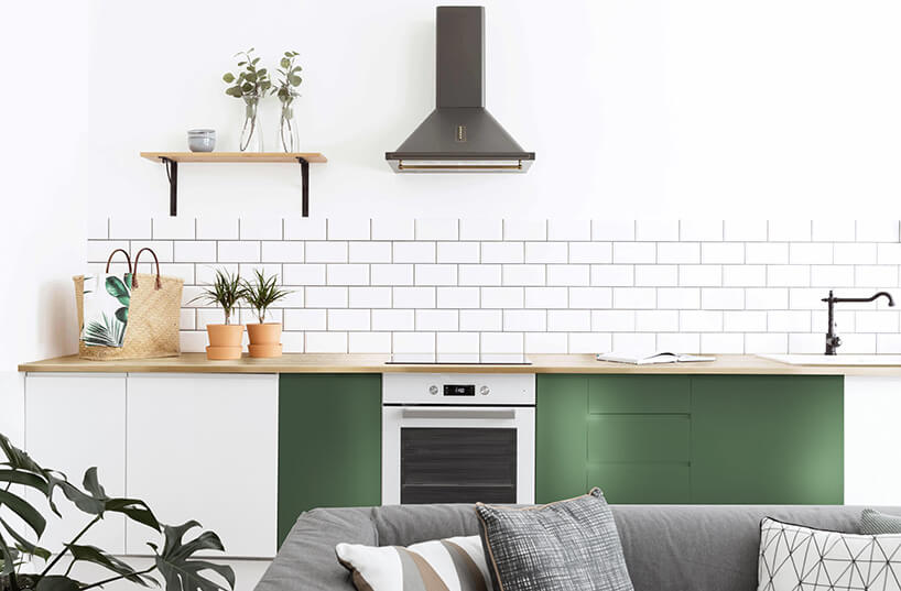 biała licówka na ścianie przy blacie kuchennym zzielonymi szafkami oraz białym piekarniku