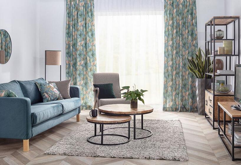 salon zstylizowaną podłogą jasno niebieska kanapa zpoduszkami iindustrialnymi meblami zczarną konstrukcją