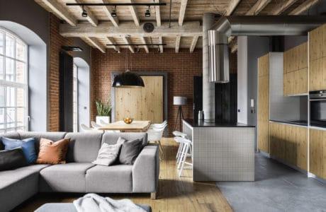 wnętrze loftowe z czerwoną starą cegłą w salonie z wygiętą chromowaną rurą wentylacyjną oraz jasno bambusowymi frontami szafek