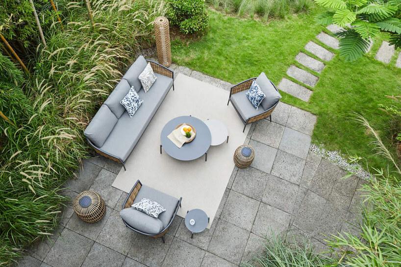 szary zestaw ogrodowy na betonowych płytach pośród wysokich traw wogrodzie