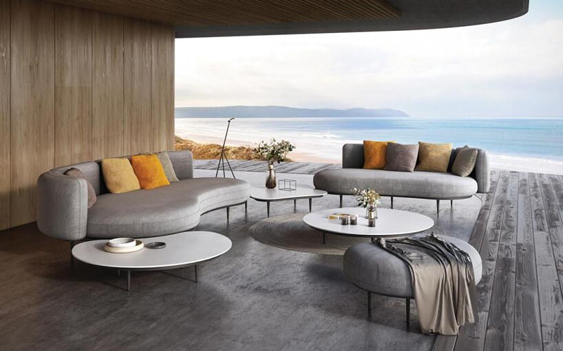 duży nowoczesny zestaw ogrodowy Organix Lounge od Royal Botania dwa duże siedziska zoparciem zdwoma dużymi białymi stolikami na tarasie zwidokiem na morze