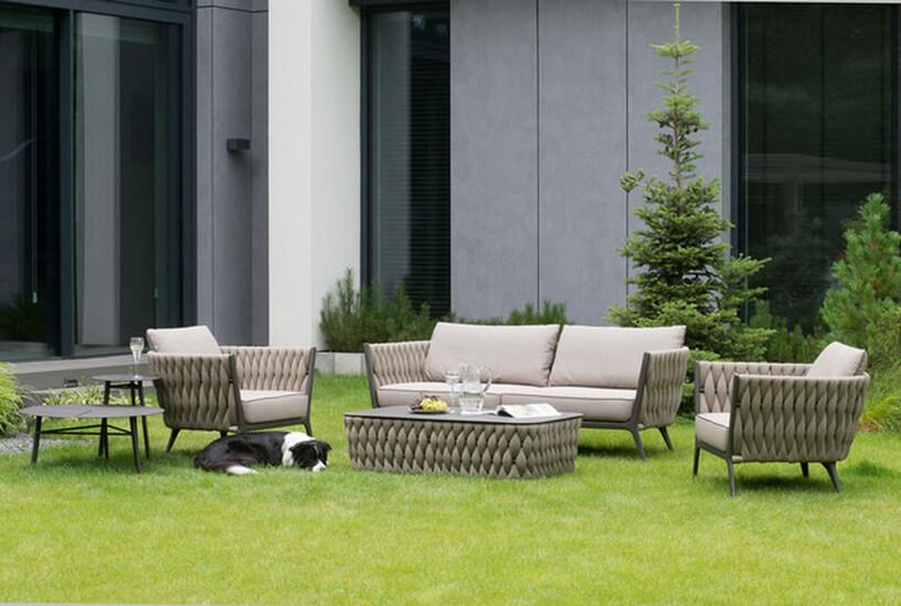 zestaw mebli ogrodowych zkolekcji Kampala od Miloo Home duża sofa zdwoma fotelami iniskim stolikiem wogrodzie na zielonej trawie