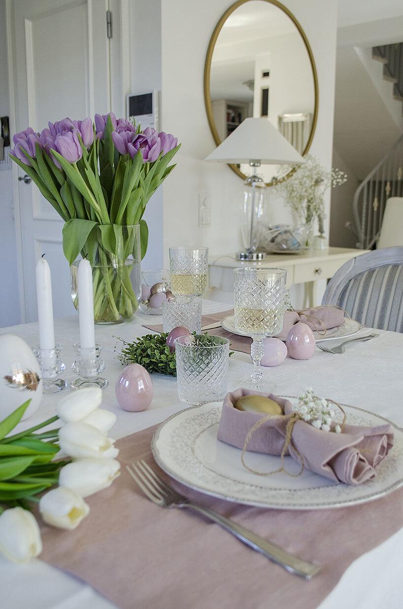 wielkanocne nakrycie stołu wkolorze antycznego różu ibieli ztulipanami izastawą szklaną