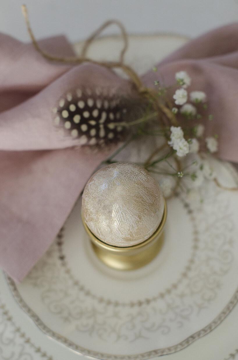 jajko zabawione na kamienny wzór biało-złoty wzłotej podstawce waranżacji zpudrowego różu