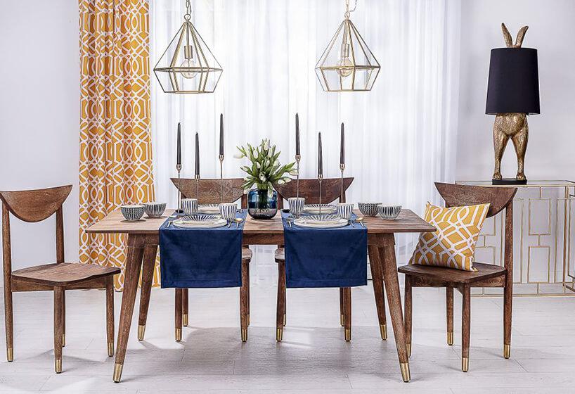 salon istół wielkanocny zgranatowymi krzesłami izasłonami wkolorze pomarańczowo-żółtym
