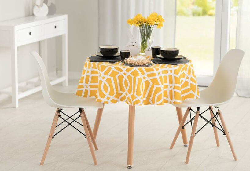 krzesła ze stołem ubranym wkolorowy żółty obrus zzastawą wkolorze czarnym