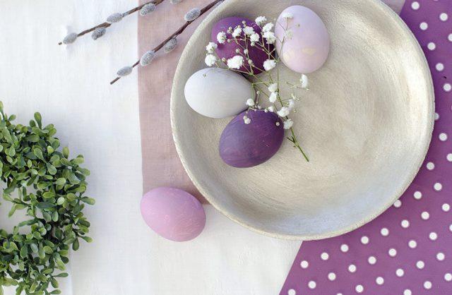kolorowe pisanki białe różowe fioletowe na białym talerzyku