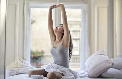 kobieta w szarej bluzce rozciągająca się na dużym łóżku