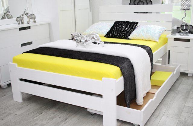 białe wysokie łózko z żółtym materacem w jasnej sypialni z szara podłogą