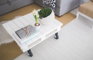 biały stolik z małej palety transportowej na czarnych gumowych kółkach