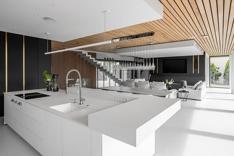 duża kuchnia zjadalnią zszarym stołem zkrzesłami przy białych schodach