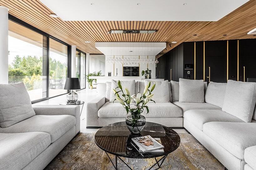salon białymi skórzanymi kanapami wsalonie zdrewnianym sufitem oraz dużymi przeszkleniami