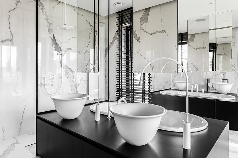 łazienka zmarmurami oraz czarnym blatem znowoczesnymi umywalkami
