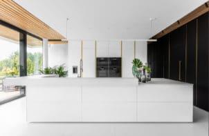 biała kuchnia w połysku przy czarnej zabudowie z szafakmi