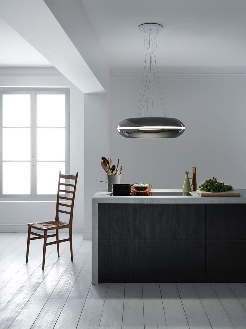 czarny okrąg wiszący na żyłkach nad czarną wyspą kuchenną obok krzesła