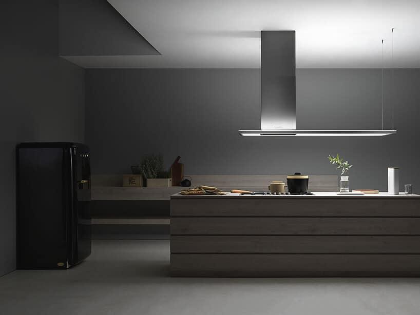 ciemna kuchnia zczarną retro lodówką oraz wyspą kuchenną wkształcie prostokąta