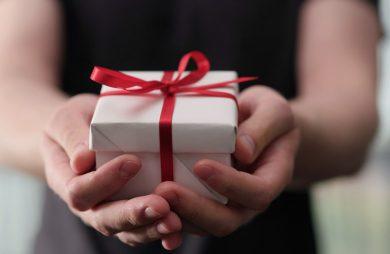 mały prezent zapakowany w biały papier z czerwoną wstążką w rękach kobiety