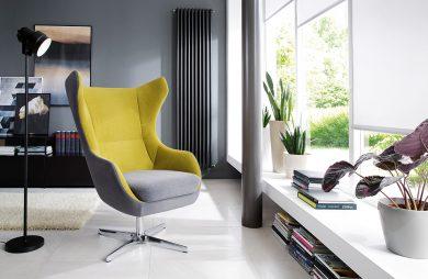 żółto szary fotel ze chromowanej centralnej nodze na białej podłodze na tle wysokiego ciemnego grzejnika