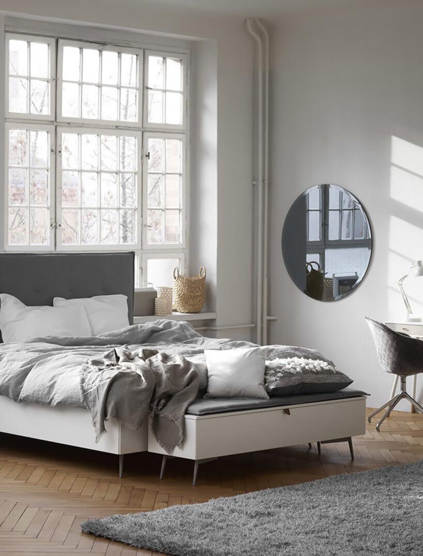 białe łóżko okrągłe lustro szare krzesło biała lampka na tle białych ścian