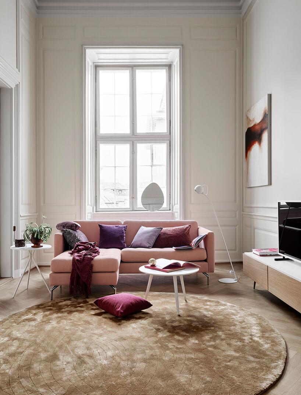 różowa kanapa ibiały stolik wjasny pokoju