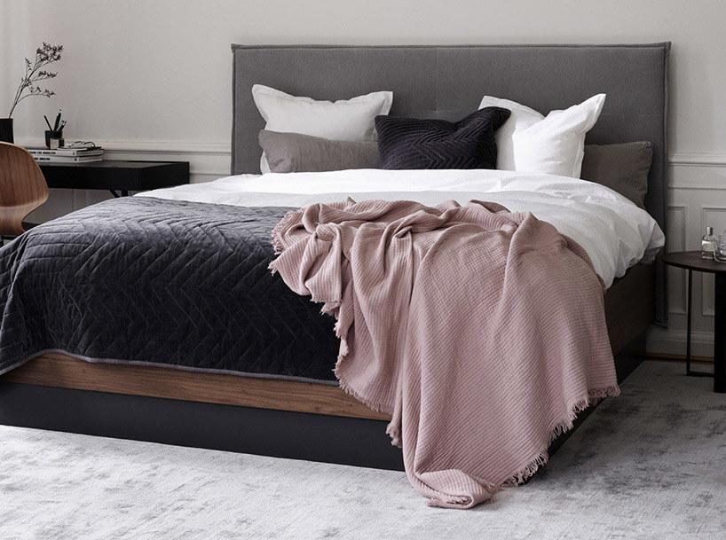 szare łóżko małżeńskie na tle białej ściany