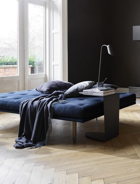 niebieskie łóżko na tle czarnej ściany