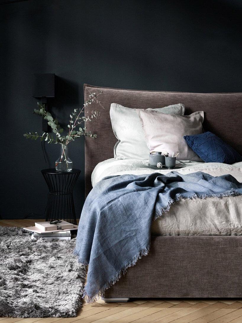 brązowe łóżko na tle czarnej ściany