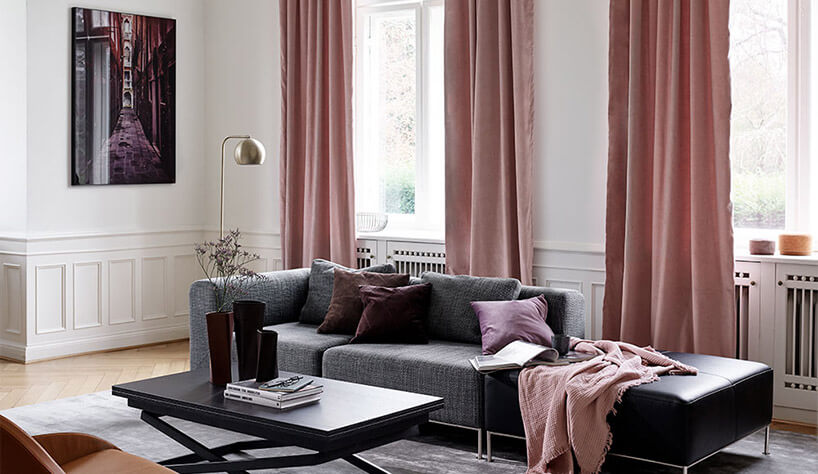 szara kanapa czarny stolik białe ściany różowe zaslony