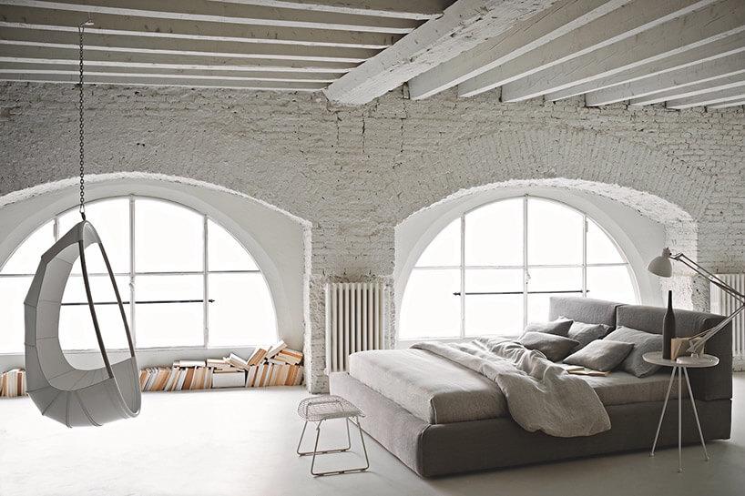 szare łóżko biała huśtawka wbiałym pomieszczeniu