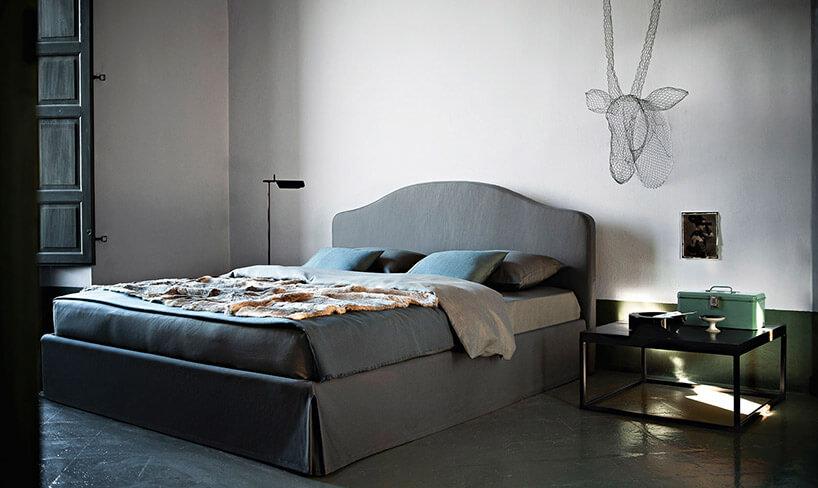 niebieskie łóżko czarny stolik nocny na tle białej ściany