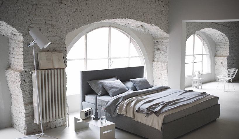 szare łóżko wbiałym pomieszczeniu