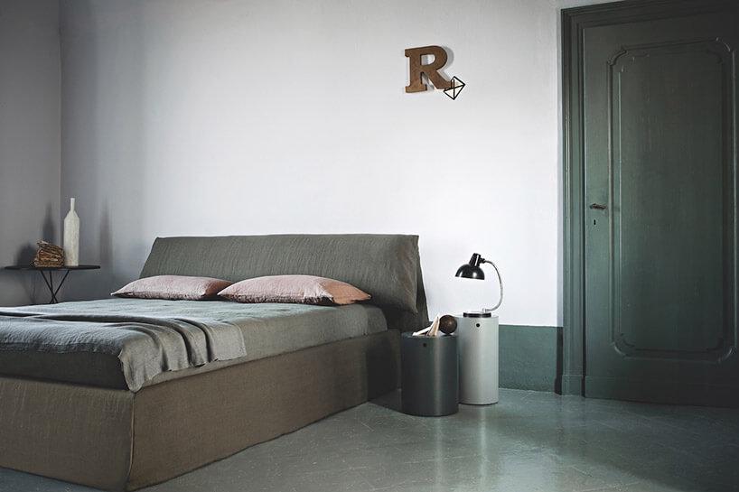 brązowo zielone łóżko zielone drzwi czarna lampka na tle białej ściany