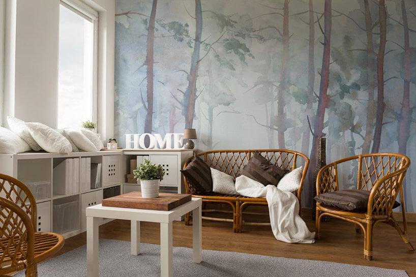 salon zmałym stolikiem wiklinową łąweczką ioftelem na tle tapety zpastelowymi drzewami