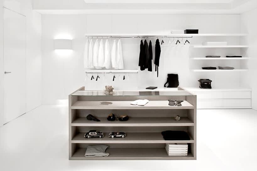 nieskazitelnie biała garderobo zpuklami na ścianie ikomodą na środku