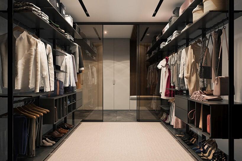 duża garderoba zkolorowymi eleganckimi ubraniami wpomieszczeniu zkremową podłogą oraz szybami odgradzającymi od korytarza