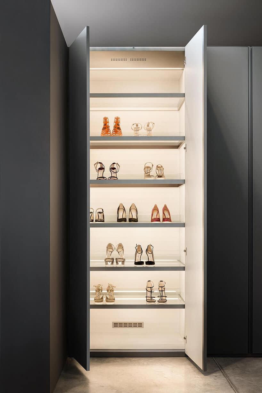 szafa dwuskrzydłowa zszarymi frontami oraz półkami zpodświetlonymi butami