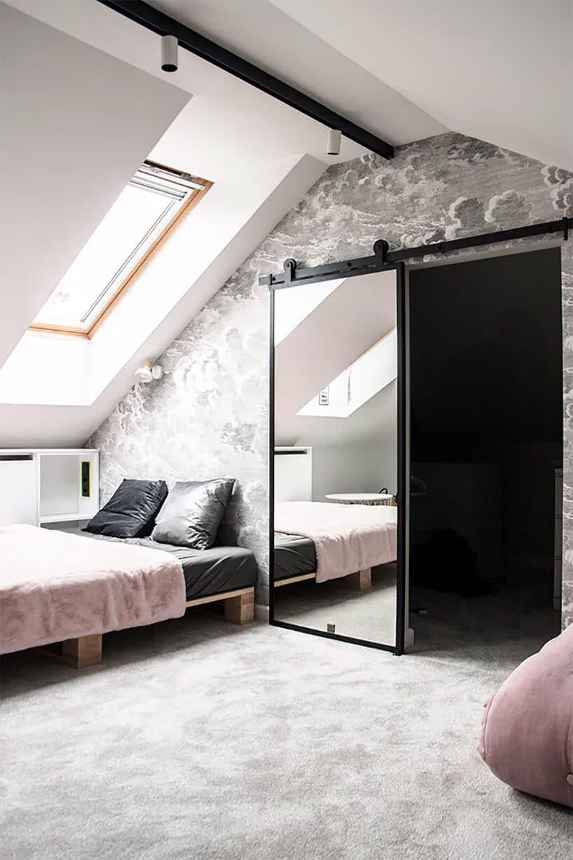 szare wnętrze zróżowymi łóżkami pod skosem