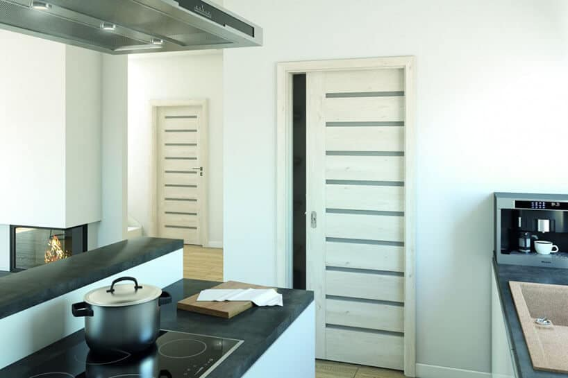 kuchnia zjasnym wnętrzem iprostymi drzwiami wkolorze białym