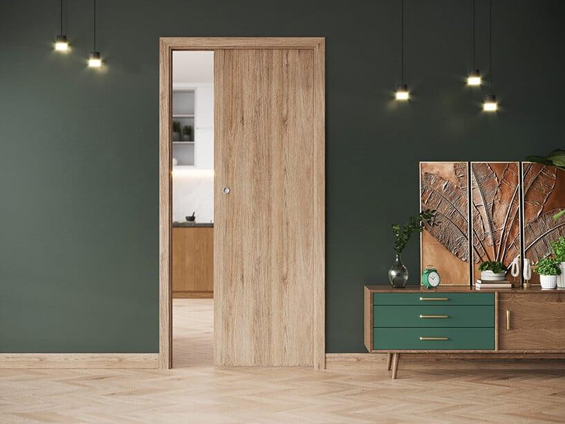 ciemno zielona ściana zjasnymi panelami ikontynuacją wformie jasnych drzwi przesuwnych