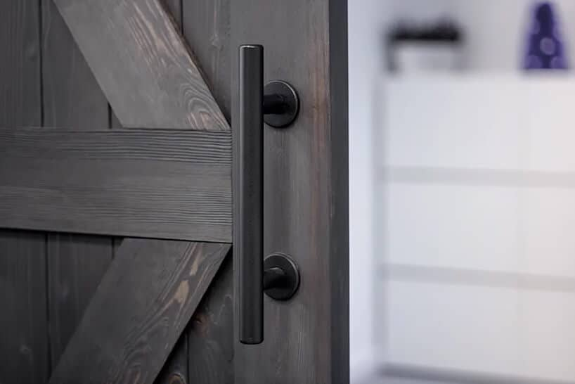 ciemno brązowe drewniane drzwi przesuwne zpionową klamką zrurki do przesuwania