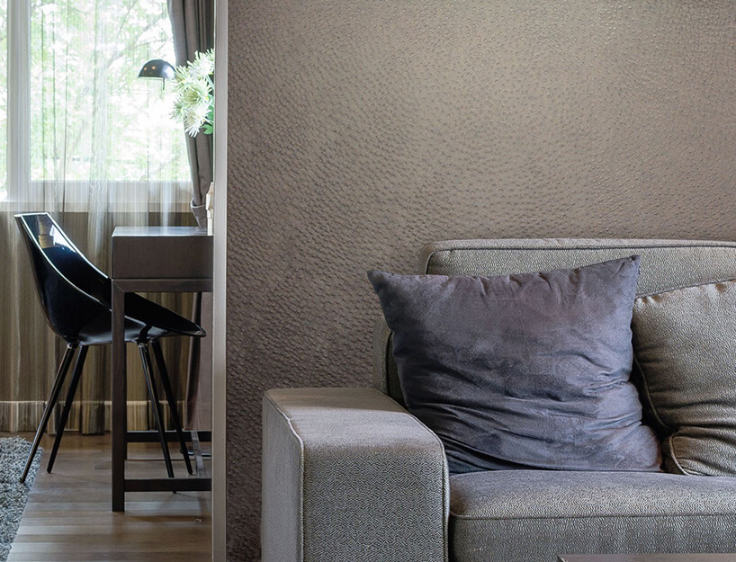 szara sofa na tle ściany ztapetą