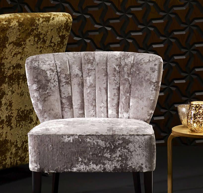 szary izłoty fotel na tle czarnej tapety