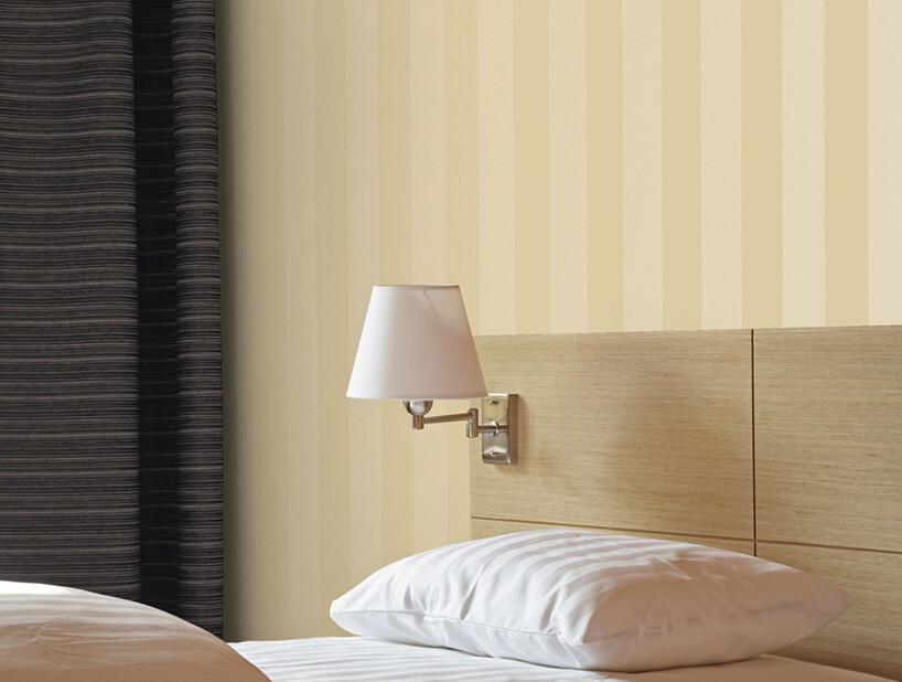 część łóżka zlampką na tle beżowej tapety