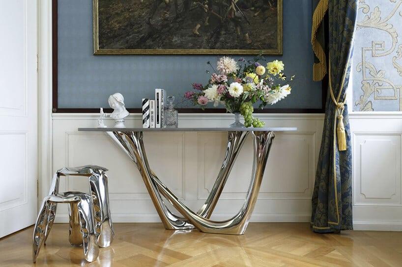 szklany stół zkwiatami pod ścianą zbiałą boazerją
