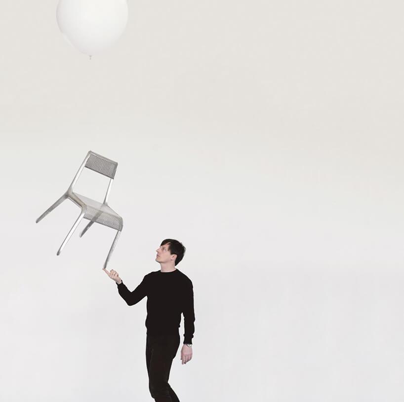 Oskar zieta trzymający wręku nowoczesne białe lekkie krzesło