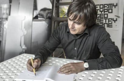 oskar zięty piszący na białym stole
