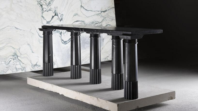 czarny marmurowy stolik na tle białej marmurowej ściany