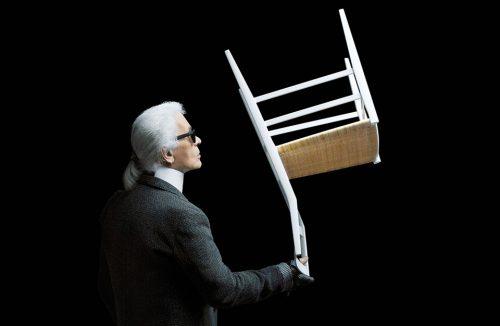 Karl Lagenferd trzymający odwrócone białe krzesło