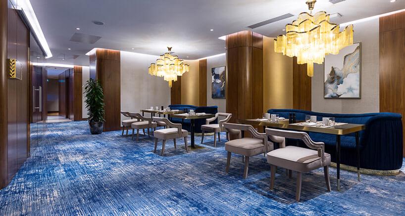 pomieszczenie zniebieskim dywanem iparoma siedziskami