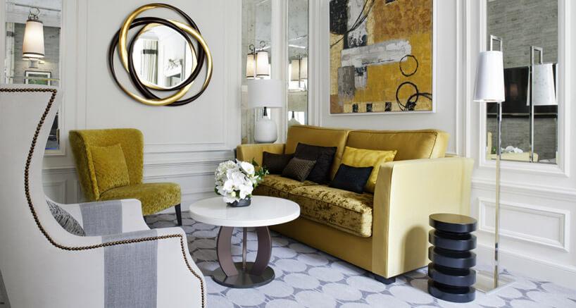 beżowa sofa ifotel zpoduszkami wjasnym pokoju